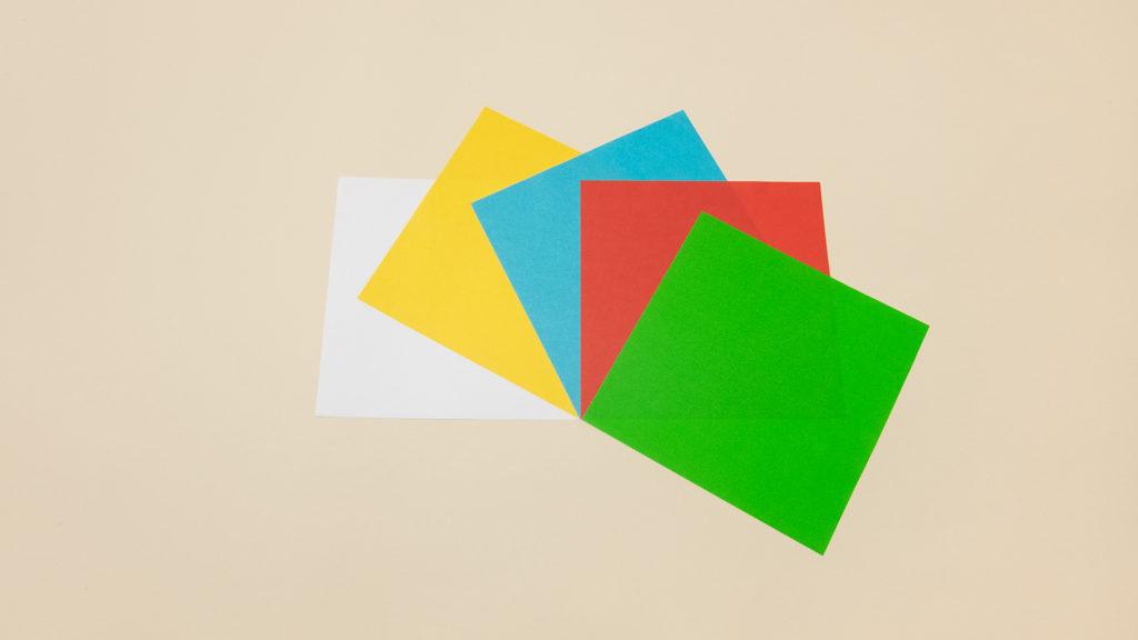 Цветные листы бумаги освещены белым светом